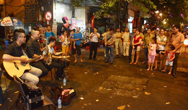 Put aside your bike and join the crowd on walking streets. Enjoy street art performance and street food. Photo courtesy of vietbao.vn